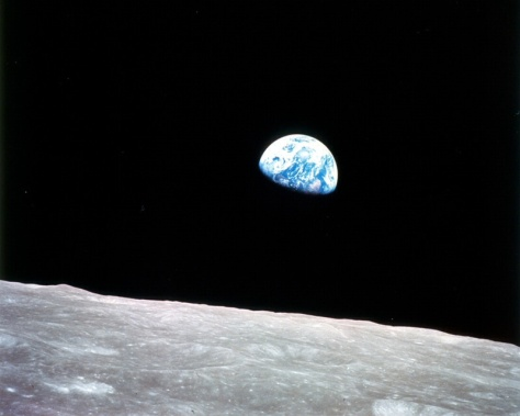 Earth seen rising in a lunar sky.