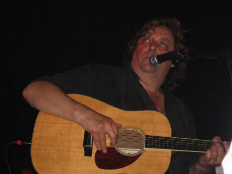 Jackie Leven playing his guitar at live performance.